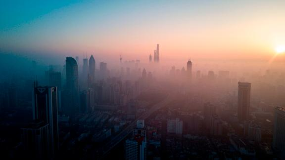TOPSHOT - This overhead photo shows the sun rising above the skyline of Shanghai on a polluted day on February 23, 2018. / AFP PHOTO / Johannes EISELE        (Photo credit should read JOHANNES EISELE/AFP/Getty Images)