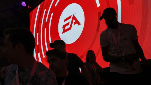 The silhouettes of attendees are seen standing in front of a Electronic Arts Inc. (EA) logo displayed on a screen during the company's EA Play event ahead of the E3 Electronic Entertainment Expo in Los Angeles, California, U.S., on Saturday, June 9, 2018. EA announced that it is introducing a higher-end version of its subscriptiongame-playing service that will include new titles such as Battlefield V and the Madden NFL 19 football game. Photographer: Patrick T. Fallon/Bloomberg via Getty Images