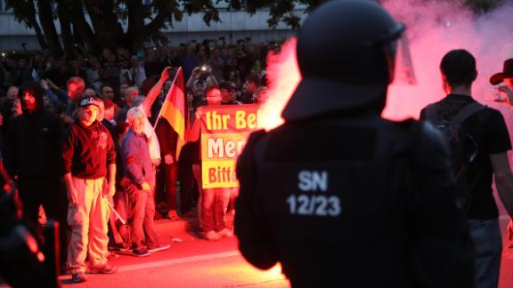 CHEMNITZ, GERMANY - AUGUST 27:  Riot police watch right-wing supporters who had gathered the day after a man was stabbed and died of his injuries on August 27, 2018 in Chemnitz, Germany. A German man died after being stabbed in the early hours yesterday following an altercation, leading a xenophobic mob of approximately 800 people to take to the streets. Today left-wing and right-wing groups of over a thousand people each confronted each other as riot police stood in between. Police announced today they have arrested a Syrian man and an Iraqi man as suspected perpetrators of the stabbing.  (Photo by Sean Gallup/Getty Images)