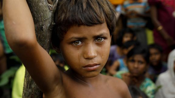 A Rohingya refugee girl looks next to newly arrived refugees who fled to Bangladesh from Myanmar in Ukhiya on September 6, 2017.