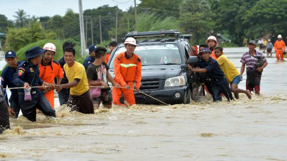 Residents negotiate a flooded road Wednesday after rampaging waters from the Swar Chaung dam spillway submerged villages in the Bago region of central Myanmar.