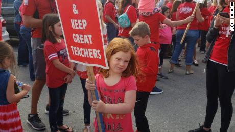 Monroe High School teacher Scott Darrow posted this image of his daughter at a protest Monday. The Monroe school year starts next Wednesday.