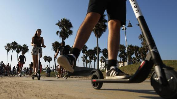 People ride Bird shared dockless electric scooters along Venice Beach on August 13, 2018 in Los Angeles, California.