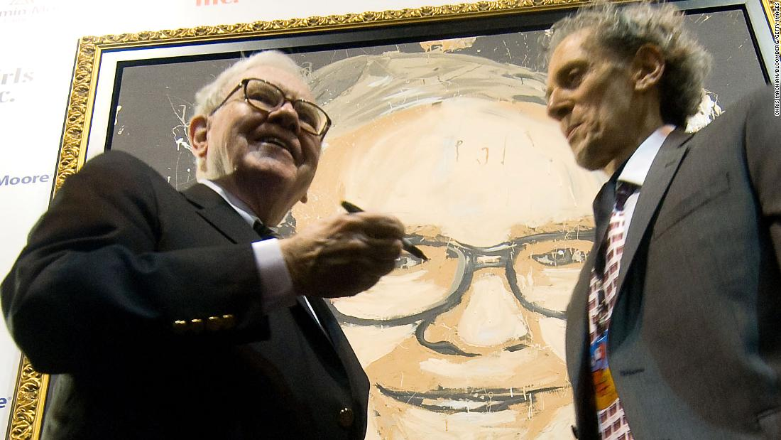 Buffett stands in front of a portrait of himself, painted by Michael Israel, in 2008.