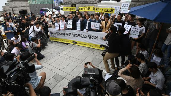 "South Korean activists and conscientious objectors to military service hold yellow banners reading ""Conscientious objection is not a crime"" during a rally outside the Constitutional Court in Seoul on June 28, 2018."