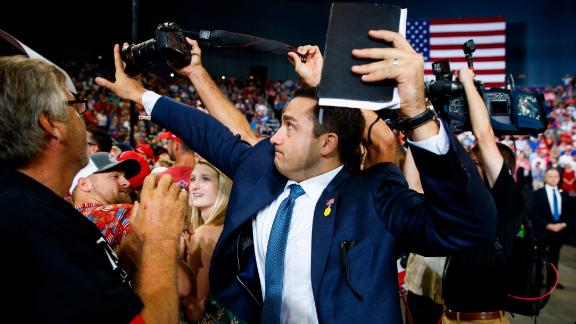 A staff member for President Donald Trump blocks a camera as a photojournalist attempts to take a photo of a protester during a campaign rally at the Ford Center, Thursday, Aug. 30, 2018, in Evansville, Ind. (AP Photo/Evan Vucci)