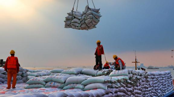 Workers transporting bags of soybean meal at a dockyard in Jiangsu province.