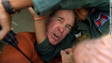 Australian filmmaker James Ricketson attempts to speak to journalists after being found guilty of espionage in Cambodia.