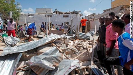 Somalis search wreckage at the scene of a blast outside the compound of a district headquarters in Mogadishu, Somalia, on Sunday, September 2.