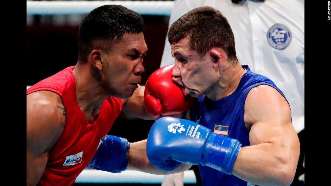 Phillippines' Eumir Felix Marcial, left, and Uzbekistan's Israil Madrimov fight in their men's middleweight boxing semifinal on Friday, August 31.
