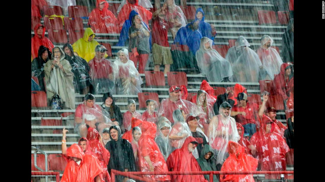 Fans at Memorial Stadium in Lincoln, Nebraska, brave the elements during a lightning and rain delay in the first half of the football game between Nebraska and Akron on Saturday, September 1. The game was eventually canceled.