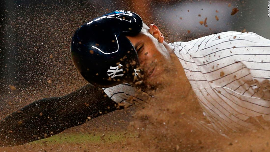 New York Yankees' Aaron Hicks dives into home plate to score on a single by Miguel Andújar against the Detroit Tigers on Thursday, August 30.