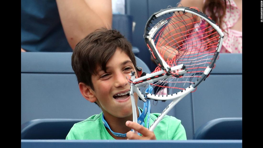 A young fan receives a broken racquet from Austria's Dominic Thiem during the US Open men's singles third round on Friday, August 31.