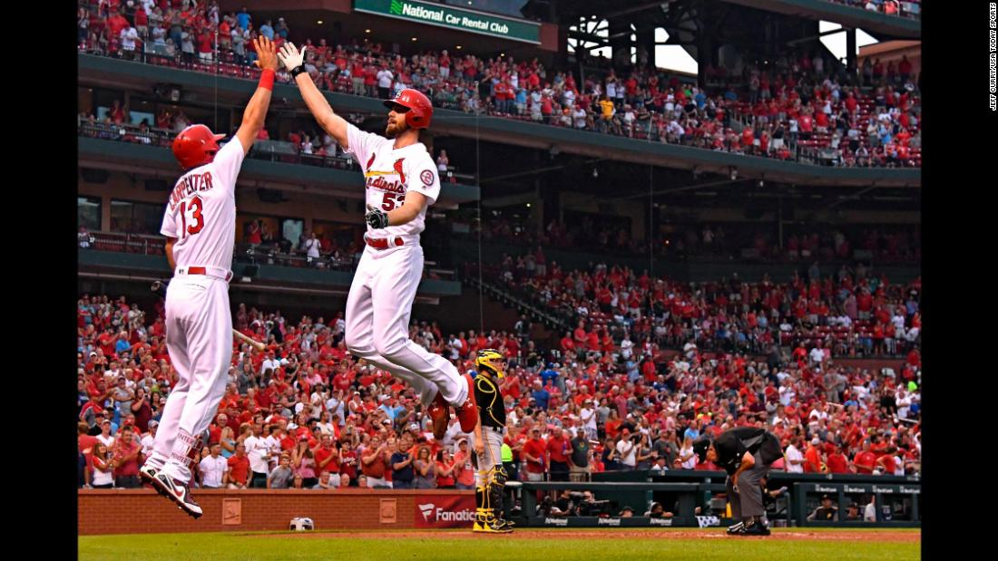 St. Louis Cardinals starting pitcher John Gant leaps to high-five third baseman Matt Carpenter after hitting a solo home run off of Pittsburgh Pirates starting pitcher Joe Musgrove during the fourth inning at Busch Stadium on Friday, August 31.