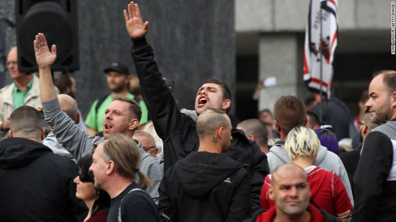 A man raises his arm in a Heil Hitler salute towards heckling leftists at a right-wing protest  in Chemnitz.