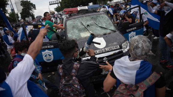 People attack a police car during a demonstration against the government in Managua on September 2, 2018.