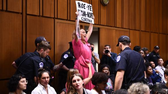 A member of Code Pink protests as US Supreme Court nominee Brett Kavanaugh arrives on the first day of his confirmation hearing in front of the US Senate on Capitol Hill in Washington DC, on September 4, 2018. - President Donald Trump's newest Supreme Court nominee Brett Kavanaugh is expected to face punishing questioning from Democrats this week over his endorsement of presidential immunity and his opposition to abortion. Some two dozen witnesses are lined up to argue for and against confirming Kavanaugh, who could swing the nine-member high court decidedly in conservatives' favor for years to come. Democrats have mobilized heavily to prevent his approval. (Photo by Brendan Smialowski / AFP)        (Photo credit should read BRENDAN SMIALOWSKI/AFP/Getty Images)