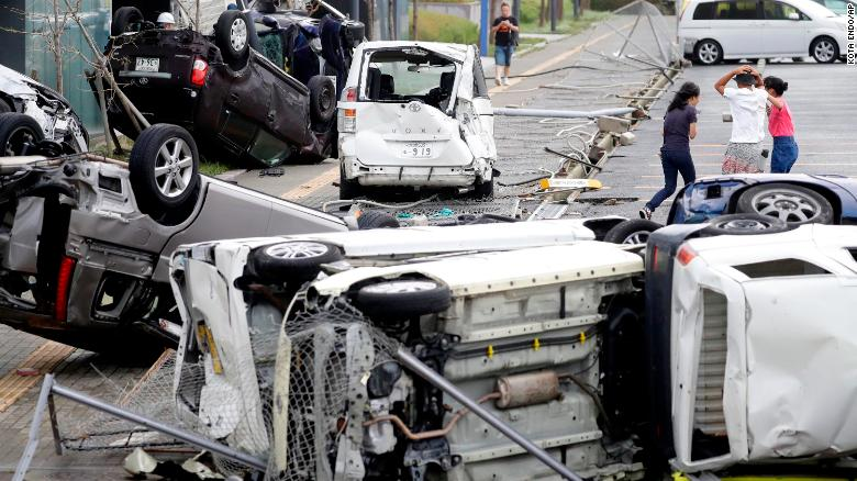 Overturned cars are seen on the street following a powerful typhoon in Osaka, in western Japan.