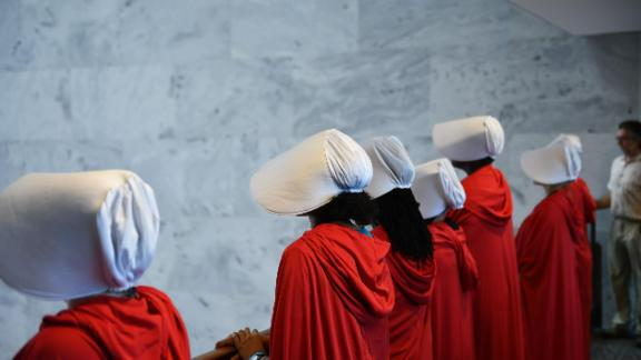 "Women dressed as characters from the novel-turned-TV series ""The Handmaid's Tale"" line up before Supreme Court nominee Brett Kavanaugh starts the first day of his confirmation hearing in front of the US Senate on Capitol Hill in Washington DC, on September 4, 2018."