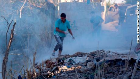 Syrians use dirt to put out a fire at the scene of a reported air strike in the district of Jisr al-Shughur, in the Idlib province, on September 4, 2018.