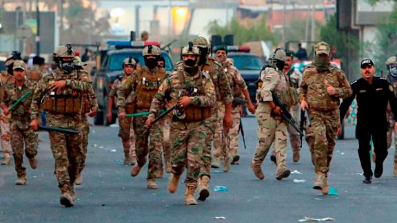 Security forces prepare to disperse protesters Sunday from outside a provincial council building.