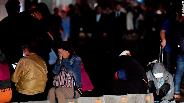 A woman covers her face as she takes shelter on a road following a strong earthquake in Sapporo.