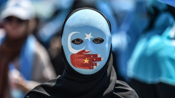 TOPSHOT - A demonstrator wearing a mask painted with the colours of the flag of East Turkestan and a hand bearing the colours of the Chinese flag attends a protest of supporters of the mostly Muslim Uighur minority and Turkish nationalists to denounce China