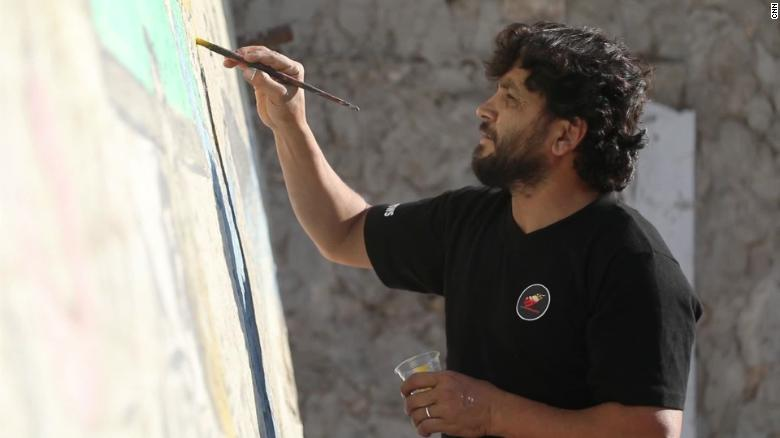 Aziz Al-Asamr works on his mural of Trump.