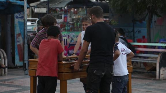Boys play foosball on the sidewalk of Idlib.