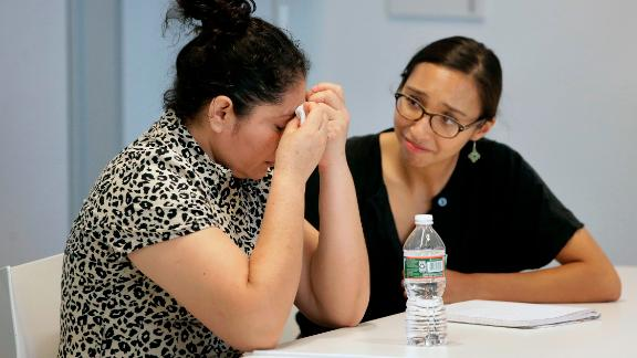 A mother from Guatemala, left, who was separated from her two children after entering the U.S. in May of 2018, receives support from translator Brenda Quintana, right, after speaking to reporters about the separation during a news conference, Thursday, September 6, 2018, in Boston.