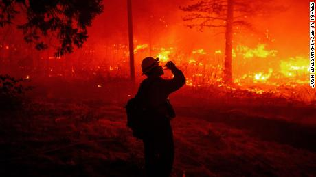 A firefighter drinks water as flames spread Thursday in Pollard Flat.