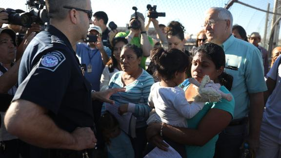 US Border Patrol agent Ray Provencia informs Angelica and Karla (who didn't want their last names used), along with Ruben Garcia, director of the Annunciation House, (R) who was helping them cross, that they will have to wait at the top of the Paso Del Norte Port of Entry, where the U.S. and Mexico border meet, for space to open up at the border processing center so they can ask for asylum on June 20, 2018 in El Paso, Texas.