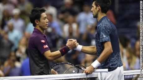 Nishikori and Djokovic shake hands following their men's singles semifinal match.