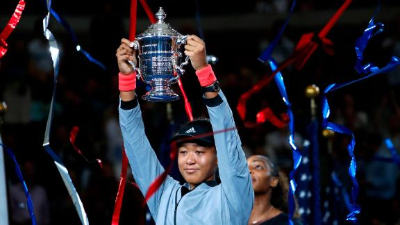 Naomi Osaka, of Japan, holds the trophy after defeating Serena Williams in the women