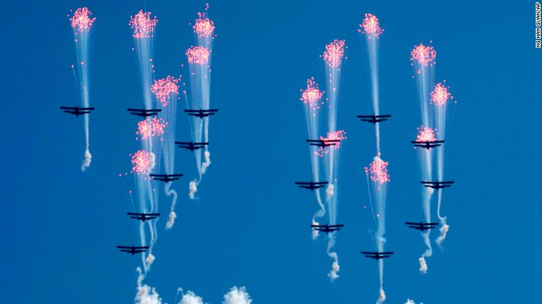 Airplanes forming the number 70 fly in formation and fire flares during the parade.