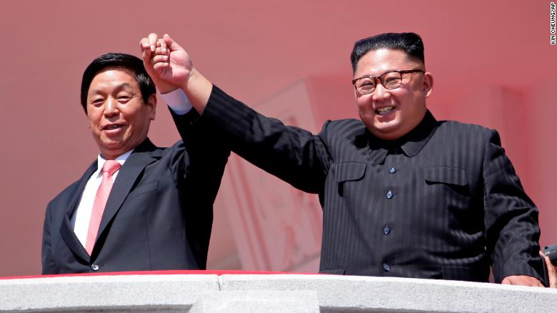 North Korean leader Kim Jong Un, right, raises hands with Chinese envoy Li Zhanshu.