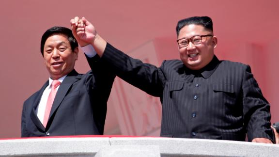 North Korean leader Kim Jong Un, right, raises hands with China's third highest ranking official, Li Zhanshu, during a parade for the 70th anniversary of North Korea's founding day in Pyongyang, North Korea, Sunday, September 9. North Korea staged a major military parade, huge rallies and will revive its iconic mass games on Sunday to mark its 70th anniversary as a nation.