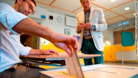 An election official casts a voter's ballot at a polling station in Stockholm on Sunday.