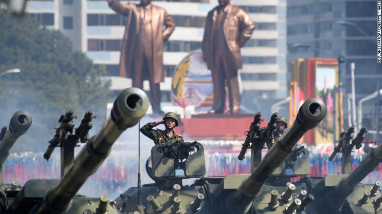 Soldiers salute as they ride tanks during a military parade and mass rally in Pyongyang's Kim Il Sung Square on Sunday.