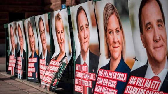 A woman walks next to election posters of (R-L) the leader of the Social Democrats and Swedish Prime Minister Stefan Loefven, Swedish Minister for Finance Magdalena Andersson and Sweden's Foreign Minister Margot Wallstrom on September 1, 2018 in Stockholm.