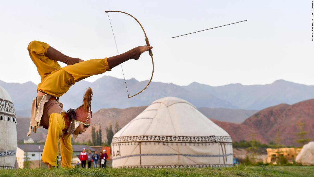 A woman shoots a bow and arrow with her feet at the 2018 World Nomad Games in the town of Cholpon-Ata, Issyk-Kul Region, Kyrgyzstan, on Tuesday, September 4. The event is held every two years and includes 37 sporting events, such as horse riding, national wrestling, martial arts, archery and traditional mind games.
