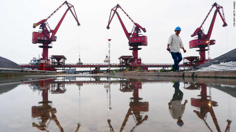 Workers walk as crane buckets transfer soybeans imported from Brazil at a port in Nantong in China's eastern Jiangsu province.