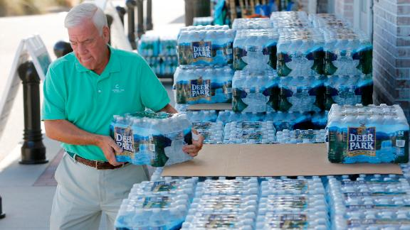 Larry Pierson, from the Isle of Palms, S.C., purchases bottled water from the Harris Teeter grocery store on the Isle of Palms in preparation for Hurricane Florence at the Isle of Palms S.C., Monday, Sept. 10, 2018. (AP Photo/Mic Smith)