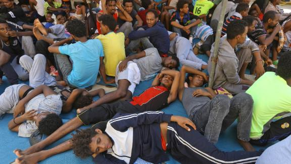 Illegal migrants sit inside the Ganzour shelter after being transferred from in the  airport road due to fighting in the Libyan capital Tripoli on September 5, 2018.