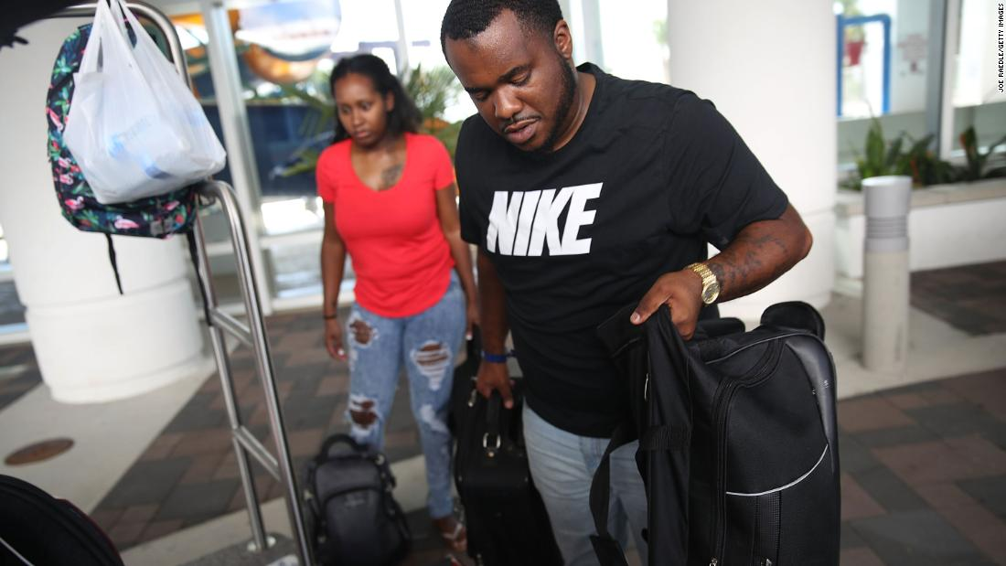 Marcus Thurston and his wife, Shenae, evacuate a hotel in Myrtle Beach, South Carolina, as they cut their vacation short on Tuesday, September 11.