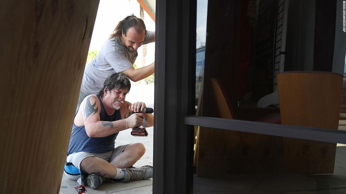 Scott Fleenor, bottom, and Jeremiah Trendell board over the windows of a business in Myrtle Beach.
