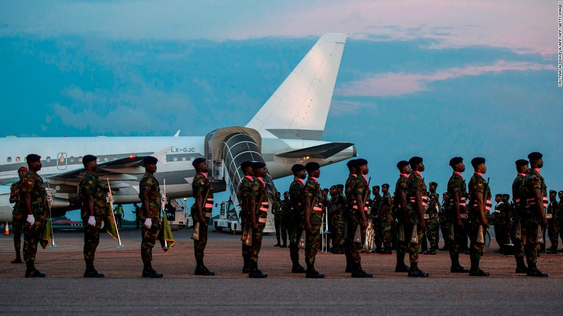 Soldiers from the Ghanaian military stand to attention as the plane carrying the remains of the late diplomat arrived on the tarmac of Kotoka International Airport.