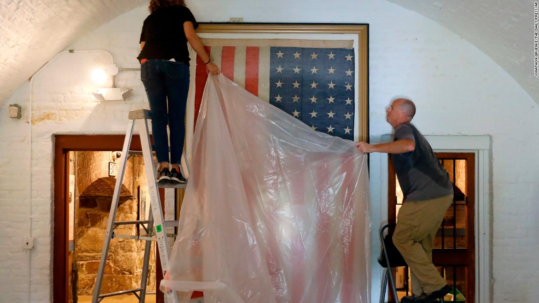 Veronica Gallardo and Robert Kelly place a plastic tarp over an American flag inside the Casemate Museum at Fort Monroe in Hampton, Virginia, on September 11.