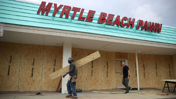 Jeff Bryant, left, and James Evans board the windows of a business in Myrtle Beach, South Carolina, on Tuesday, September 11.