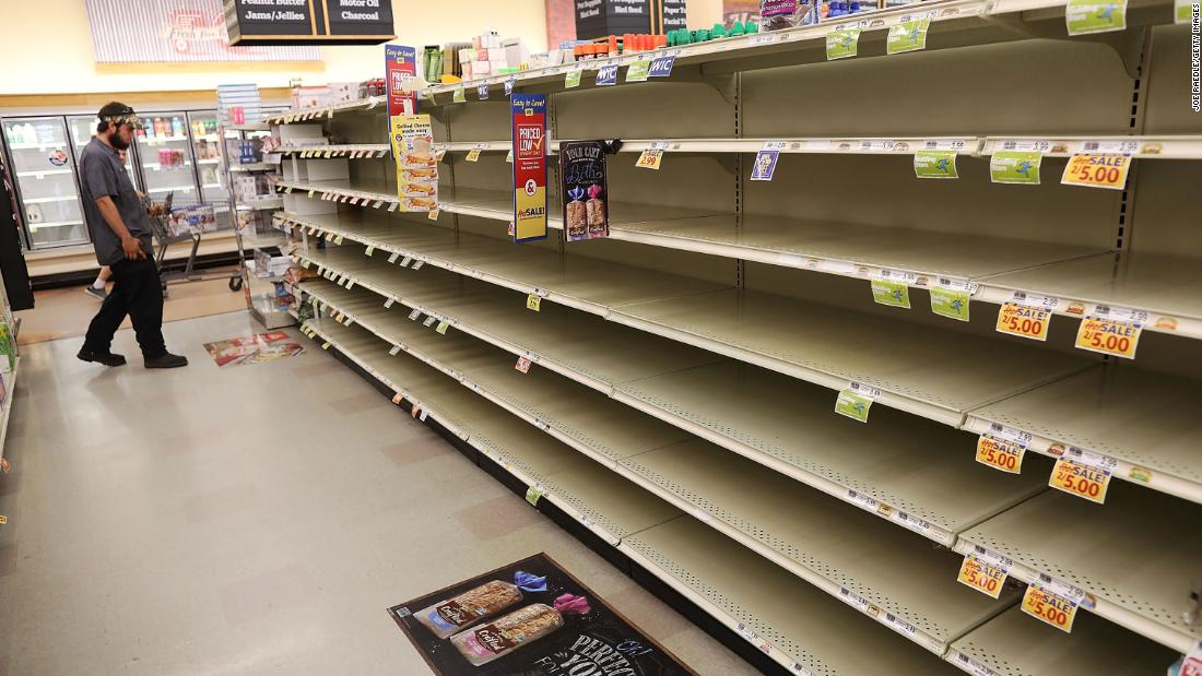A man eyes a store's bare bread shelves as people stock up on food in Myrtle Beach on September 11.